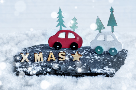 Christmas decoration of wooden XMAS letters and wooden cars in a snow scene Stock Photo