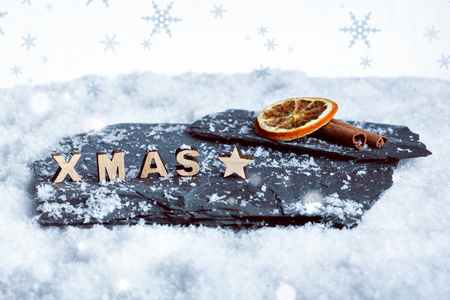 Christmas decoration of wooden XMAS letters, a slice of orange and cinnamon in the snow Stock Photo