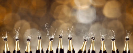 Splashing Champagne bottles with blurred lights in the background