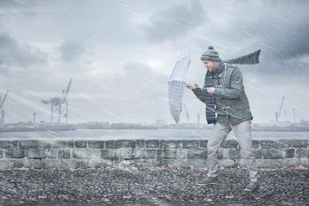 Peatón con paraguas se enfrenta a fuertes vientos y lluvia