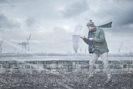 Pedestrian with an umbrella is facing strong wind and rain Stockfoto