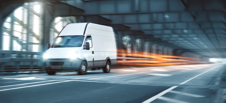 Van driving on a road through an industrial style bridge