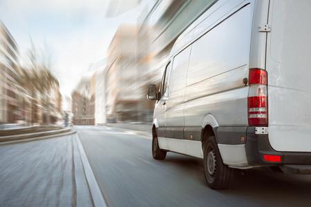 Weißer Transporter, der in der Stadt fährt