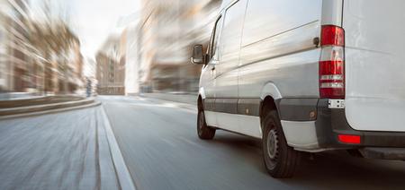 Witte transporter die door de stad rijdt
