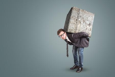 Homme d'affaires portant une grosse et lourde pierre sur le dos