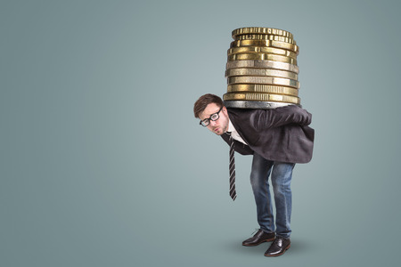 Businessman carrying a giant stack of coins on his back Standard-Bild