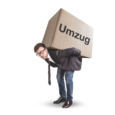 A man is carrying a large cardboard box with the German word move 스톡 콘텐츠