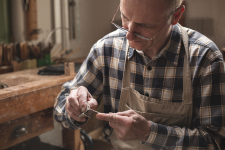 Mature artisan in a workshop sanding down a violin bow manually