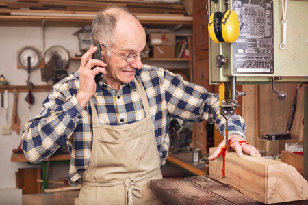 Mature man having a work accident on a band saw Stock fotó
