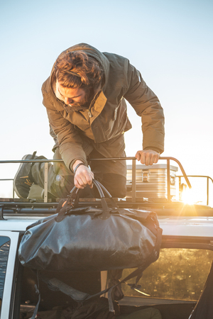 A man is loading luggage on the roof of a camper van while the sun is setting Zdjęcie Seryjne