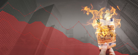 Falling stock prices ?? burning 50? ? banknote in front of a declining graph Фото со стока