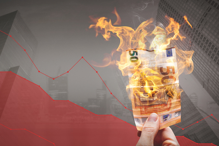Loosing money concept? burning 50?,? bill in front of a declining graph