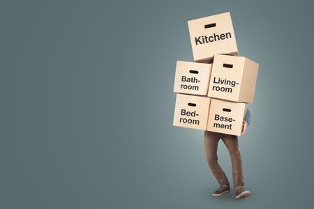 Mann trägt einen großen Stapel Umzugskartons, die mit verschiedenen Räumen beschriftet sind