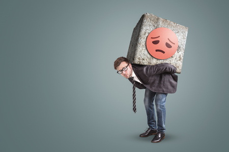 Unhappy entrepreneur bending under a large stone on his back