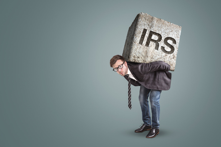 Businessman bending under a heavy stone with the letters IRS printed on it - tax office concept Фото со стока