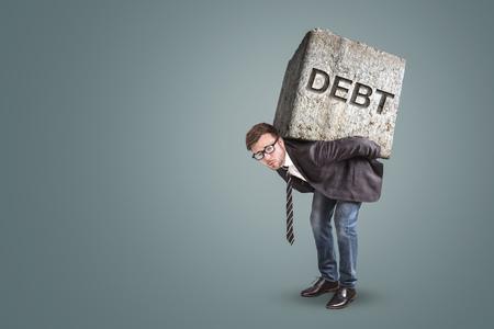 Concept of a businessman bending under the burden of heavy debts Archivio Fotografico