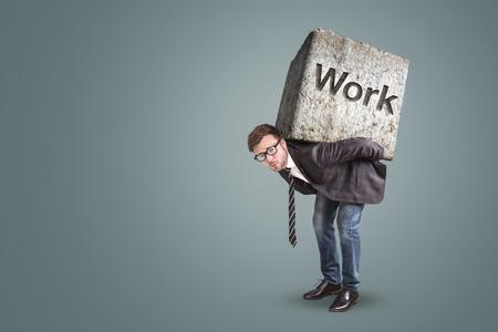 Concetto di un imprenditore che si piega sotto un carico di lavoro pesante