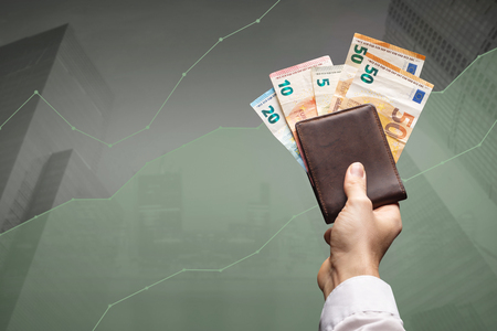 High financial gains concept - a wallet packed with Euro notes in front of a rising graph Фото со стока