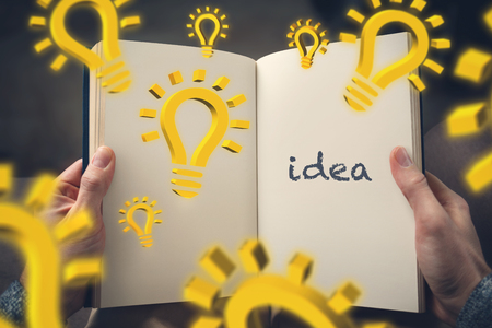 Inspiration through reading - hand-held book with 3d lightbulb symbols and the word idea on one page Фото со стока