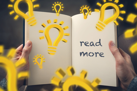 read more? concept - hand-held book with 3d lightbulb symbols