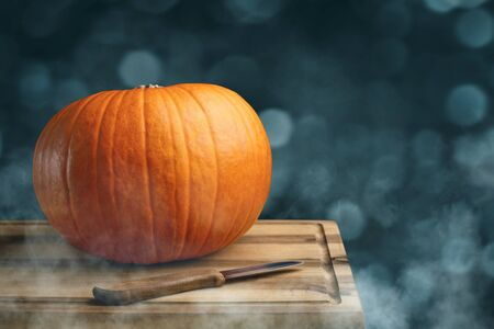 Orange pumpkin and a knife on a wooden board? preparation for Halloween