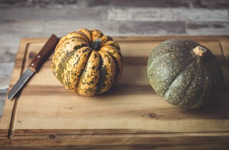 Small pumpkins and a knife on a wooden cutting board Фото со стока