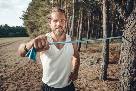 Young man using a resistance band to work out in nature Фото со стока
