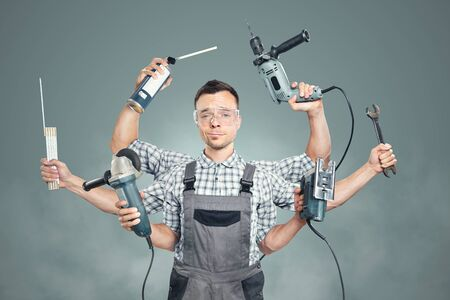 Funny portrait of a craftsman with 6 arms and tools 免版税图像