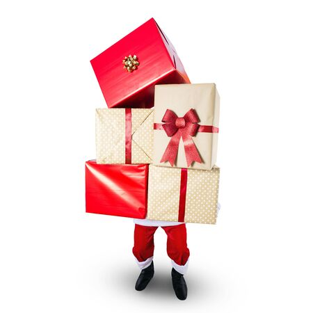 Santa Claus carrying a big stack of Christmas presents - isolated on white