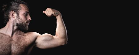 Muscular man with a beard doing a biceps pose panorama Zdjęcie Seryjne