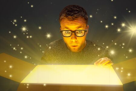 Amazed man next to a magically glowing parcel