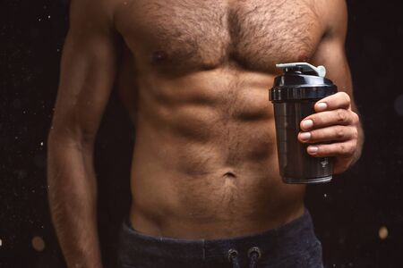 Shirtless torso of a muscular man with a shaker in one hand