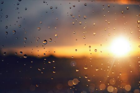 Raindrops on a windowpane at sunset