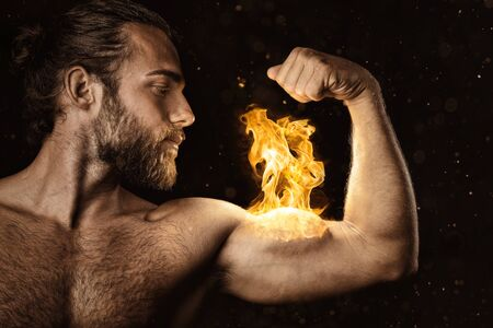 Strong man with a biceps on fire