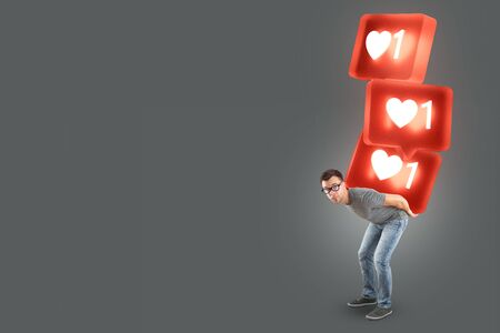 Man carrying a stack of large social media like symbols