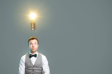 Man looking towards a light bulb above his head Zdjęcie Seryjne