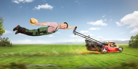 Funny gardener being pulled across the lawn by a lawn mower Imagens