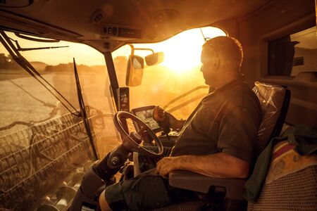 Operator inside a combine harvester at sunset