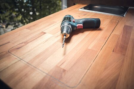 Cordless power drill on a wooden counter Stock fotó