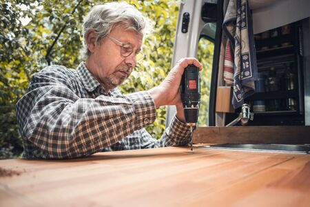 Senior man working on his caravan with a power drill