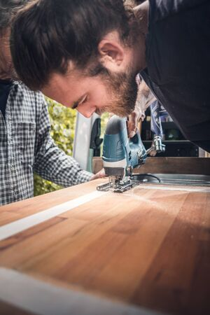 Man using a jigsaw to cut a wooden countertop