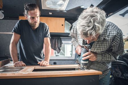 Father and adult son working on a camper van conversion