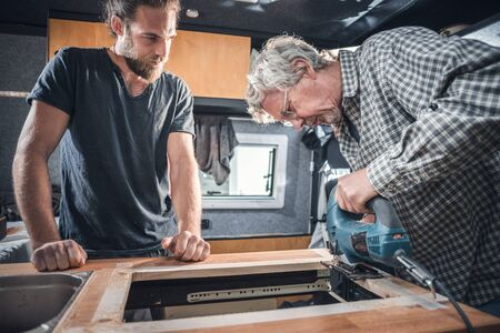 Father and adult son working on the interior of a camper van