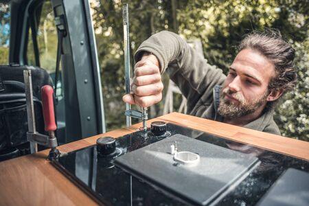 Man installing a gas stove into a camper van