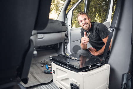 Man inside a van using heat shrink tubing on an electrical cable