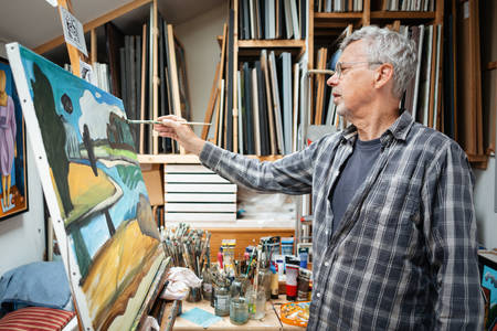 Senior artist painting in his studio