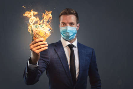 Businessman with a protective face mask is loosing money