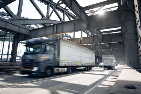 Truck with a trailer driving over an industrial style bridge 版權商用圖片 - 154899782