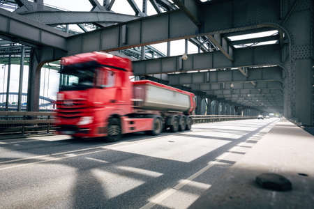 Red truck driving over an industrial style bridge Standard-Bild