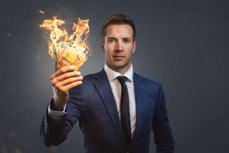 Businessman holding burning money in his hand